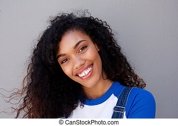 Close up beautiful young african american woman smiling against gray backgorund
