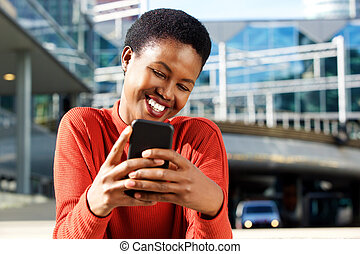 Close up beautiful young african american woman smiling and looking at cellphone