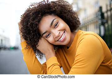 Close up beautiful young african american woman smiling with curly hair
