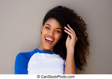 Close up beautiful young african american woman smiling with hand in hair against gray wall