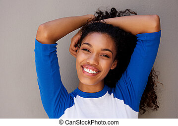 Close up beautiful young african american woman smiling with hand in hair