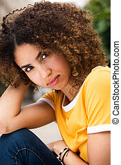 Close up beautiful young african american woman with curly hair sitting outside