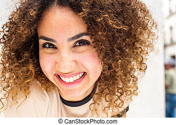 Close up beautiful young african american woman with curly hair smiling against white wall