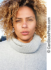 Close up beautiful young african american woman with curly hair staring