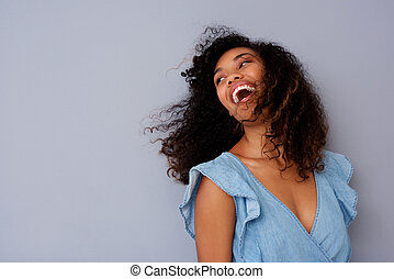 Close up beautiful young black woman laughing against gray wall