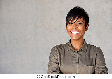 Close up beautiful young black woman smiling against gray wall