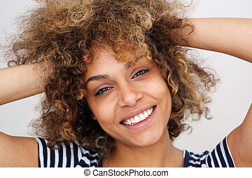 Close up beautiful young black woman smiling with hands in hair
