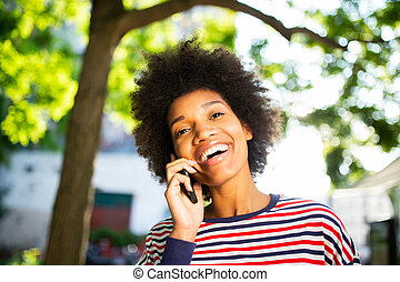 Close up beautiful young black woman with afro hair smiling and talking with mobile phone in park