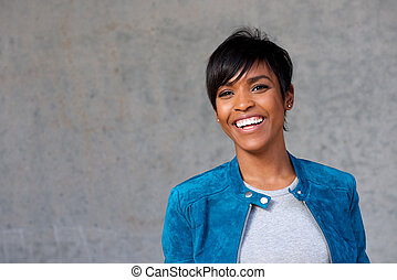 Close up beautiful young black woman with blue jacket smiling