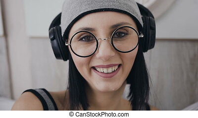 Close up. Beautiful young brunette girl in a goggles sitting to indoors she listening to music in black headphones and looking at the camera and smiling