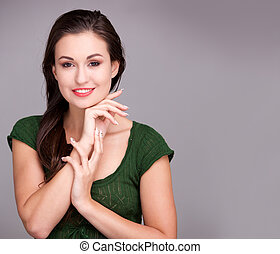 Close up beautiful young woman smiling against gray wall