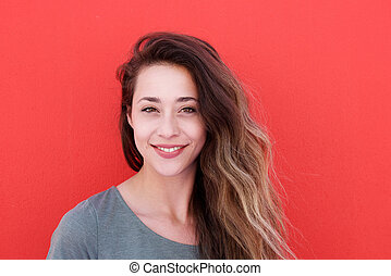 Close up beautiful young woman smiling against red background
