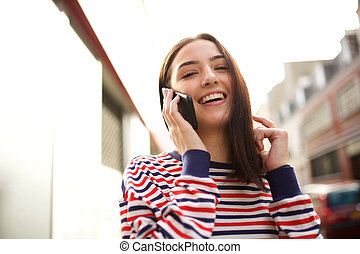 Close up beautiful young woman smiling and talking with mobile phone in city