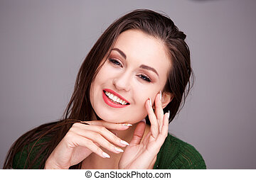 Close up beautiful young woman smiling with hands on face