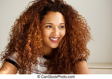 Close up beautiful young woman with curly hair smiling