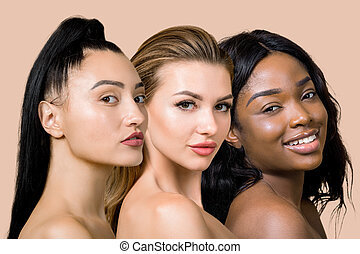 Close up beauty collage portrait of three young multiracial female models with naked shoulders and beautiful pure skin, looking on camera, on light beige studio background. World beauty