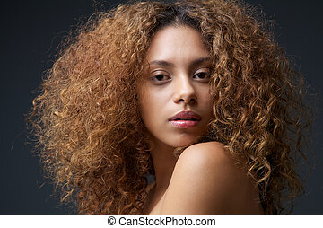 Close up beauty portrait of a beautiful female fashion model with curly hair