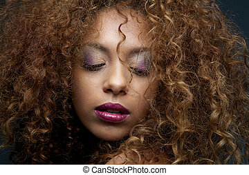 Close up beauty portrait of a female fashion model with curly hair and make up