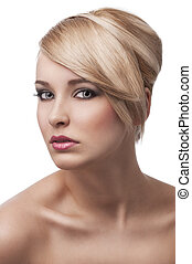 close up beauty portrait of a young and cute blond girl with hair style over white. Her face is turned three quarters, she looks in to the lens with actractive eyes