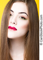 Close up beauty portrait of young white girl with creative makeup and hair isolated on yellow background.
