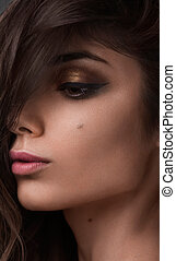 Close-up beauty shot of young pretty model with gold make-up. Eyeliner. Golden makeup and natural lipstick