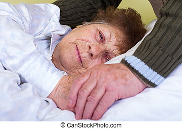 Close up picture of a bedridden woman with her husband's hands