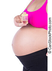close-up belly of pregnant woman with urine bottle on white background