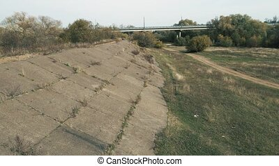Close-up birds-eye view of the old dam away from the reservoir. Concrete slabs lie on a slope overgrown with grass and bushes. The concept of hydraulic structures. Warm summer day, soft light.