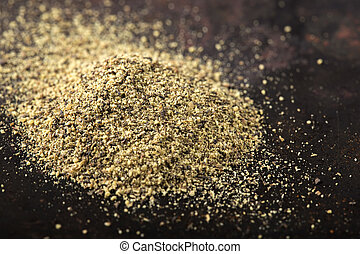 Close - up Black pepper powder on a dark rusty background