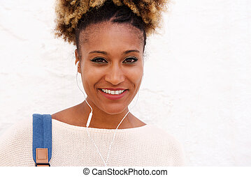 Close up black woman with earphone standing against white wall