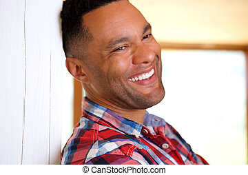 Close up black young man leaning against wall and laughing