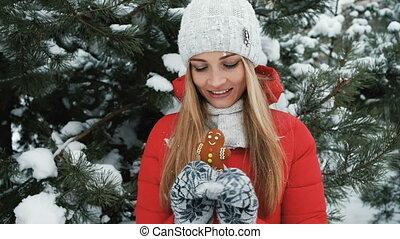 Close up blond woman walks, eat gingerbread in winter landscape
