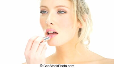 blonde woman applying her lipstick makeup