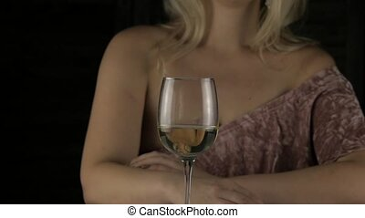 close-up blonde woman drinks champagne alone in the dark....