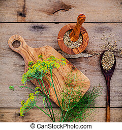 Close up blossoming branch of fennel and dried fennel seeds on rustic wooden background with flat lay.