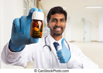 Close-up bottle of pills held by doctor