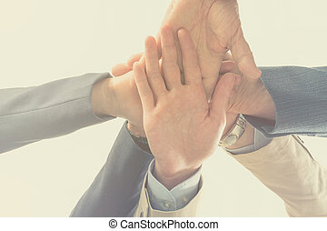 Close up bottom view business people putting their hands together. Arms consolidation, Teamwork concept.