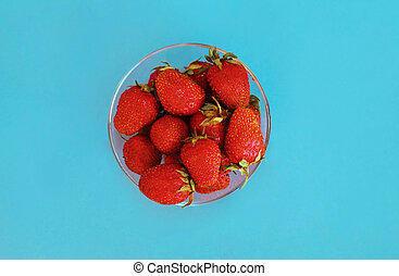 Close up bowl of fresh strawberry on a blue background, top view
