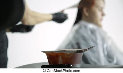 close-up bowl of red paint, colorist stirs with a brush dye...