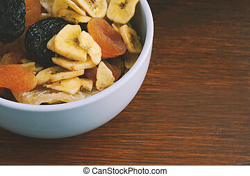 Close up bowl with different dried fruits on wooden background