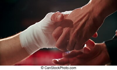 Close up boxing trainer or manager wrapping hands of a boxer...