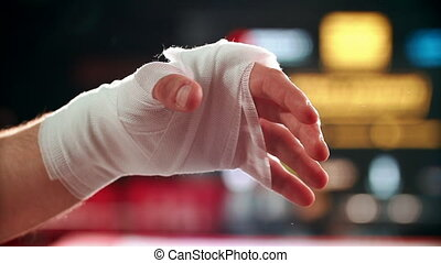 Close up boxing trainer or manager wrapping hands of a boxer reparing for boxing match