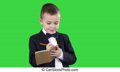 Close up. Boy in a formal clothes writing in check list or notebook on a Green Screen, Chroma Key. Professional shot in 4K resolution. 016. You can use it e.g. in your commercial video, education, business, presentation, broadcast