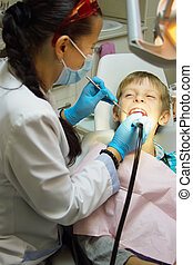 Close-up  boy opening his mouth wide during inspection of oral cavity by dentist