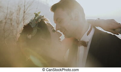 Close up. Bride and groom in love walking together in sunny mountain. Wedding day