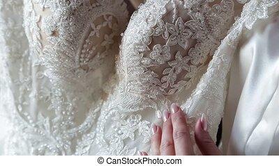 close up, bride hand strokes a wedding dress.