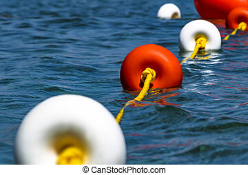 Close-up bright red and white coloers buoys on the surface of the water. Depth marks. Safety on water.