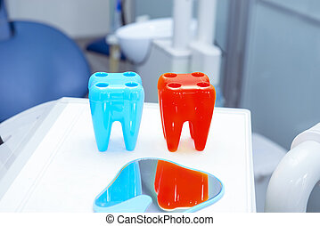 Close-up bright toothbrush holders in form of tooth and dental instruments in dentist's office. Tools close-up. Dentistry