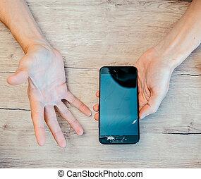 broken smartphone in the hands of a young man.
