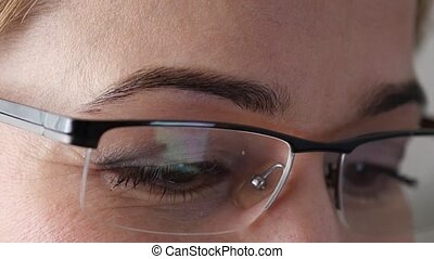 Close-up brown woman eye in glasses. Woman using a...